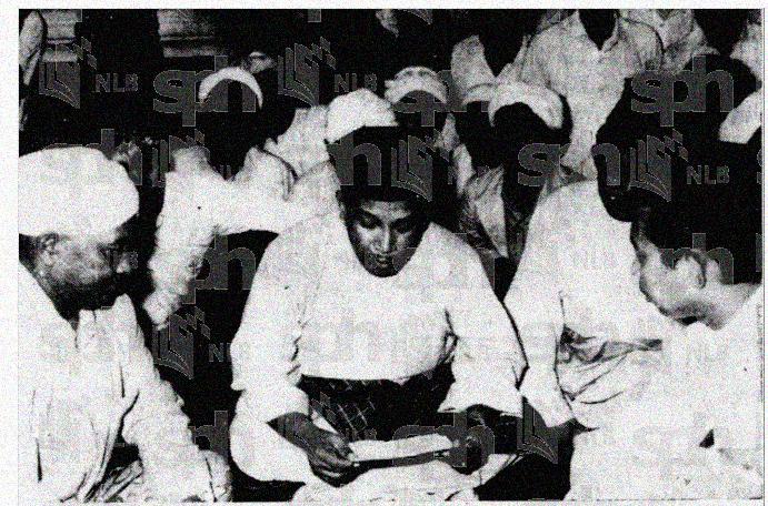 Datuk Mohamad Asri b. Muda (tengah), Menteri Besar Kelantan dari PAS sedang bersumpah di dalam Masjid Muhammadi Kota Bharu. Tengku Razaleigh Hamzah (kiri), Timbalan Ketua Perhubungan UMNO Kelantan menjadi saksi dan wakil kepada Perdana Menteri. Ehsan National Library Board Singapore.